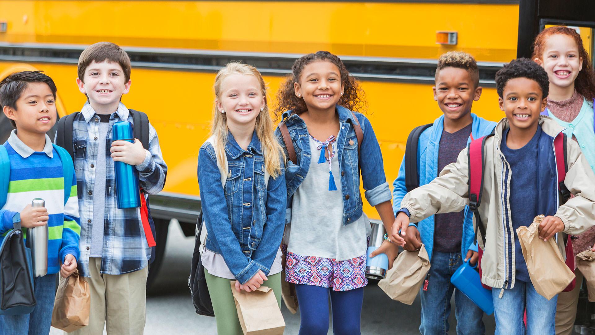 Children standing in front of bus