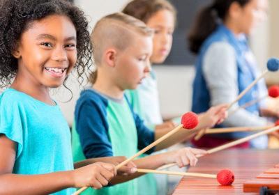 School age kids playing xylophone